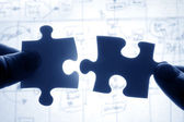 Hands trying to fit two puzzle pieces together — Stock Photo