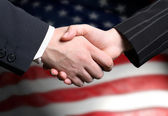Hand shake and a American flag in the background — Stok fotoğraf