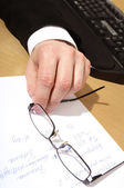 Man holding eyeglasses over paper — Stock Photo