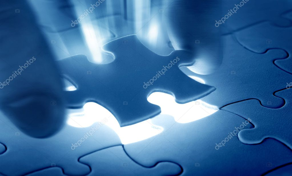 Hands placing last piece of a Puzzle  Stock Photo #4231040