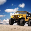 Photo of a Yellow Jeep at the beach - Stock Photo