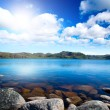 Blue lake idill under cloudy sky - Stock Photo