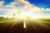 Asphalt road in green meadow. Sunset — Stock Photo