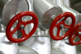 Red valves with stainless steel pipes — Stock Photo