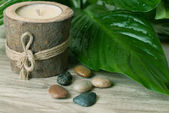 Spa. Wood candle with stones and leafs. — Stock Photo