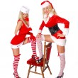 Two sexy christmas girls with red chair — Stock Photo