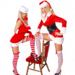 Royalty-Free Stock Photo: Two sexy christmas girls with red chair