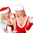 Two christmas girls give a present at each other — Stock Photo #4326738