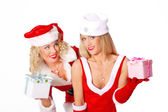 Two christmas girls give a present at each other — Stock Photo
