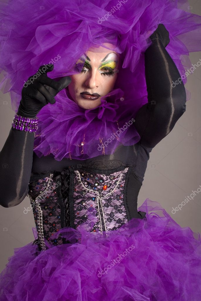 Drag queen in violet dress standing on gray background  Stock Photo #4136177