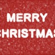 Merry Christmas hand writting text on red background with snowflakes - Stock Photo