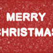Merry Christmas hand writting text on red background with snowflakes — Stock Photo #4151770