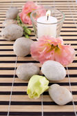 Stones with candle on bamboo mate — Stock Photo