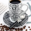 Stylish balck and white coffee mug with brown coffee beans — Stock Photo
