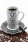 Coffee mug with burned coffee beans — Stock Photo