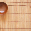 Chopsticks with wooden bowl on bamboo matting background — Stock Photo #5343290