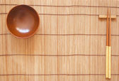 Chopsticks with wooden bowl on bamboo matting background — Stock Photo