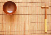 Chopsticks with wooden bowl on bamboo matting background — Stockfoto