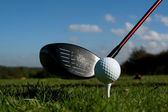 Golf driver and ball on tee blue sky — Stock Photo