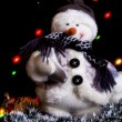 Snowman with a festoon lights and tinsel. — Stock Photo