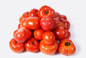 Red tomatoes laid by a pyramid on a white background — Stock Photo