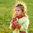 Foto Stock: Little girl eating red apple