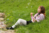 Beautiful girl is casting bubbles into the wind — Stock Photo