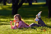 Beautiful girl licking candy in the park — Stock Photo