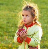 Little girl eating a red apple — Stok fotoğraf