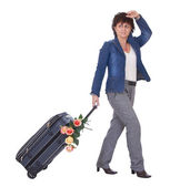 A woman traveler waving hand and holding luggage with flowers — Stock Photo