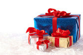 Colorful gift boxes on snow isolated on white background — Stock Photo
