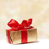 Golden gift box with red bow on blurred background — Stock Photo