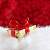 üzerinde kırmızı bulanık karşı beyaz kürk kırmızı kurdele ile altın hediye kutusu — Stok fotoğraf