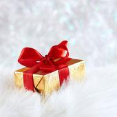 золотая подарочная коробка с красной лентой на белый мех против серебро размытие — Стоковое фото