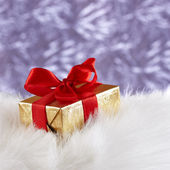 Golden gift box with red ribbon on white fur against blue blurre — Stockfoto