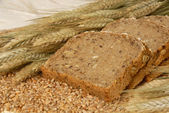 Bread slices and natural cereals — Stock Photo