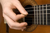 Guitar player's right hand picking the strings — Stock Photo