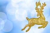 Christmas bokeh background with golden reindeer — Stock Photo