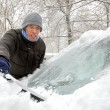 Stock Photo: Removing snow from the car