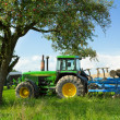 Tractor blending in a rural landscape - Stock Photo