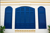 Blue window shutters on cream wall — Stock Photo