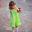 The charming child walks a road and admires beautiful orange flower — Stock Photo #4298742