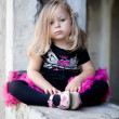 Stock Photo: Lovely toddler blonde girl sits on ruins