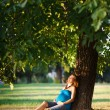Beautiful pregnant woman sitting under a tree in park — Stock Photo #4298790
