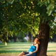 Beautiful pregnant woman sitting under a tree in park - Stock Photo