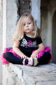 Lovely toddler blonde girl sits on ruins — Stock Photo