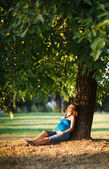 Beautiful pregnant woman sitting under a tree in park — Stock Photo