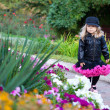 Little fashionable girl walking in flower park — Stock Photo