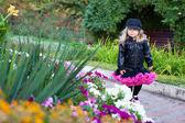 Modna dziewczynka spaceru w parku kwiat — Zdjęcie stockowe