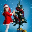 Amusing Santa girl decorating Christmas tree - Stock Photo